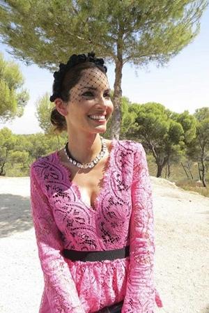 invitee de mariage avec robe en dentelle rose et chapeau voilette noir