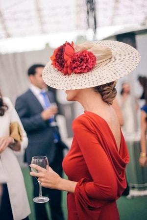 tenue invitee de mariage rouge avec grand chapeau en paille et fleurs rouge